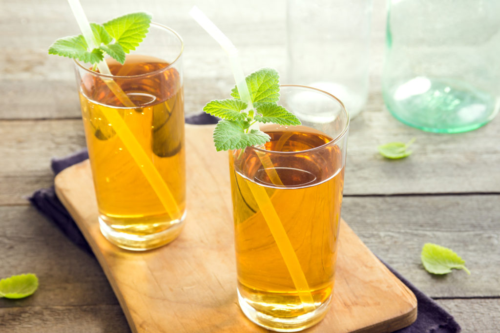 Kombucha tea super food pro biotic beverage in glasses with mint on wooden background - homemade healthy organic fermented probiotic drink