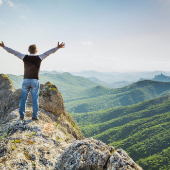 A man stands high in the mountains with his hands up